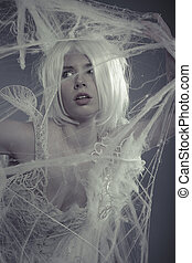 Portrait beautiful woman trapped in a spider web with a white violin, lace dress
