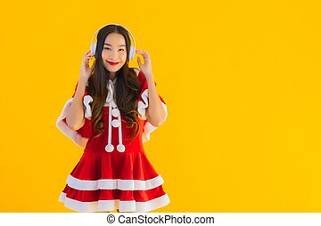 Portrait beautiful young asian christmas clothes and hat listen for music