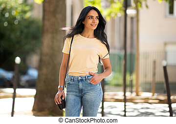 beautiful young smiling hispanic woman in city with purse