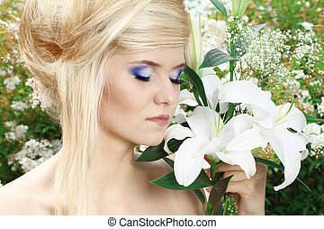 Portrait beauty make up of blonde young woman with white lily, nature outdoors
