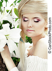 Portrait beauty make up of blonde young woman with white lily, nature
