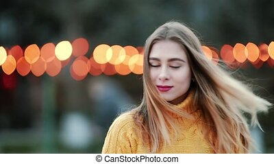 Portrait Blonde looks at camera Smiles and laughs background of yellow lights wind blows in the city