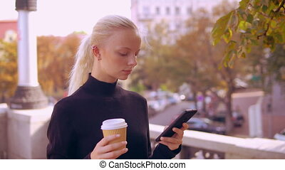 portrait blonde use phone in town - girl using smartphone...