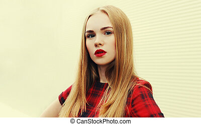 Portrait blonde young woman with red lips wearing dress over wall background