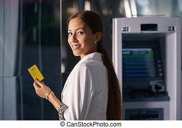 Portrait business woman withdraw cash machine card