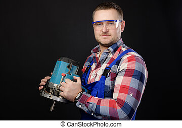 Portrait Caucasian man builder carpenter in a shirt and overalls with an electric tool in his hands. Studio portrait of friendly artisan businessman