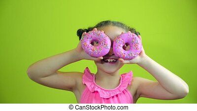 Portrait child attractive little girl holding donuts with icing to her hands smiling looks at the camera and brings them to her face looking to look at collection of sweet donuts with pink icing.