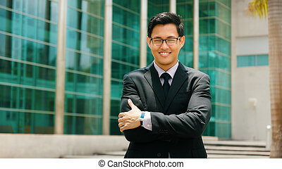 Portrait Chinese Businessman With Arms Crossed Smiling Outside Office