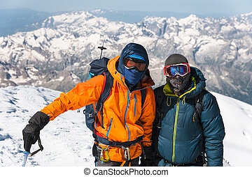 Portrait climber in a down jacket and harness he is standing next to his friend on the way to the top of a snow-capped mountain