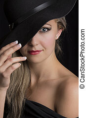 Portrait close-up of a beautiful blond woman with black hat