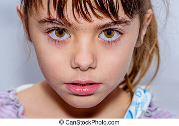 Portrait close up of a beautiful little girl with amazing brown eyes