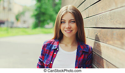 Portrait close up of beautiful young woman posing in a city