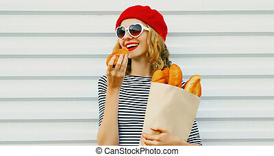 Portrait close up of cheerful woman wearing a french red beret holding paper bag with long white bread baguette over a white background