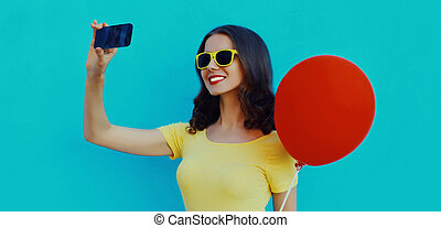 Portrait close up of woman with red balloon taking selfie by phone on a blue background