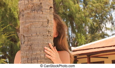 closeup blond girl in red looks out of palm trunk and speaks