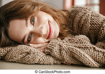 Portrait closeup of smiling lovely woman with brown curly hair, looking on camera while resting in cafe and lying on her arms