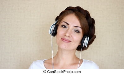 Portrait closeup woman in headphones listening to a musical song on light background.