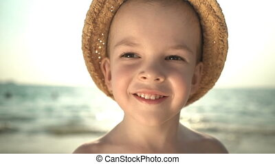 portrait cute boy in a straw hat on the beach
