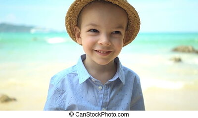 portrait cute boy in a straw hat on the beach.