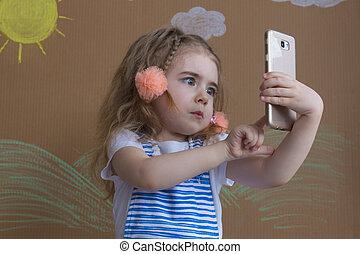 portrait cute girl makes selfie with a cell phone. Adorable smiling toddler kid taking a selfie photo with smartphone