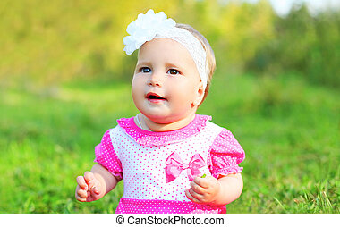 Portrait cute little girl child sitting on grass in summer day