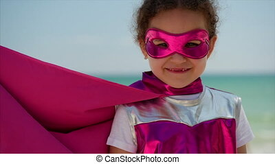 Portrait Cute Little Girl in the Superhero Costume, Dressed in a Pink Cloak and the Mask of the Hero. Plays on the Background Sea and Blue Sky and Clouds. Concept of a Happy Childhood.