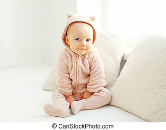 Portrait cute smiling baby sitting in white room at home near window