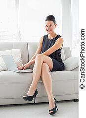 portrait, de, a, beau, puits habillé, femme aide ordinateur portatif, sur, sofa