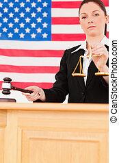 portrait, de, a, jeune, juge, frappement, a, marteau, et, tenue, balances justice, à, une, drapeau américain, dans, les, fond