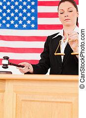 portrait, de, a, mignon, juge, frappement, a, marteau, et, tenue, balances justice, à, une, drapeau américain, dans, les, fond