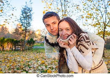 portrait, de, couple heureux, amusant, dans, automne, parc, sur, a, ensoleillé, diminuez jour