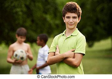 portrait, de, garçon, et, amis, football jouant, dans parc