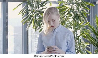 portrait, de, jeune, femme affaires, est, dactylographie, message, sur, elle, smartphone, marchant, throught, ensoleillé, salle, lent, motion.