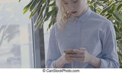 portrait, de, jeune, femme affaires, qui, est, dactylographie, message, sur, elle, smartphone, dans, clair, salle, lent, motion.