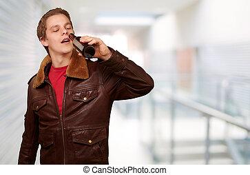 portrait, de, jeune homme, boire, bière, à, entrée, de, bâtiment moderne