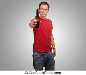 portrait, de, jeune homme, tenue, bière, sur, gris, fond