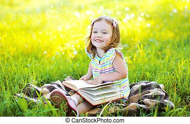 portrait, de, peu, fille souriante, enfant livre, s'asseoir herbe, dans, ensoleillé, jour été
