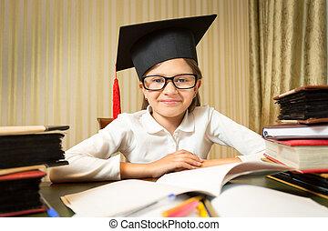 portrait, de, souriant petite fille, dans, remise de diplomes, chapeau, séance table