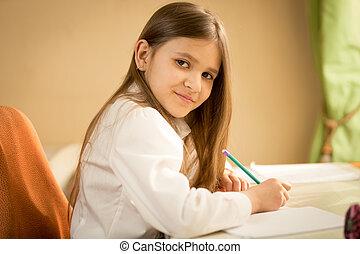 portrait, de, sourire, brunette, girl, dans, chemise blanche, asseyant, bureau, et, faire, devoirs