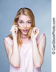 Portrait d'une jeune femme ?tonn?e, les cheveux devant la bouche