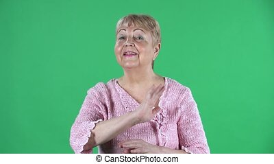 Portrait elderly woman is strictly gesturing with hands crossed making X shape meaning denial saying NO. Gray haired grandmother with short hair in a pink sweater on green screen at studio. Close up