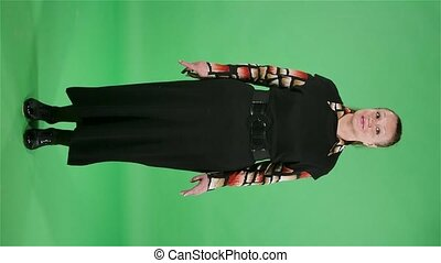 Portrait elderly woman looking around and making a hush gesture secret. Brunette granny in black dress on green screen at studio. Slow motion. Vertical video