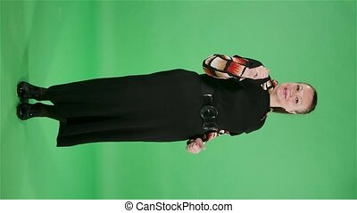 Portrait elderly woman looking at camera and showing thumbs up gesture. Brunette granny in black dress on green screen at studio. Slow motion. Vertical video
