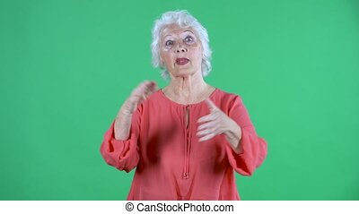 Portrait elderly woman looking at the camera clapping her hands with wow happy joy and delight. Gray haired grandmother in red blouse on green screen at studio. Close up