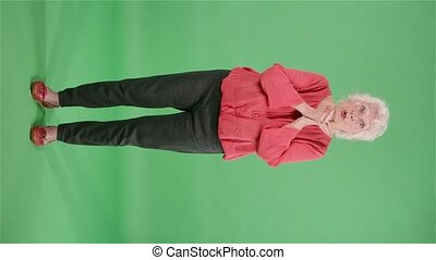 Portrait elderly woman looking at the camera keeping palm together and asking for something . Gray haired grandmother in red blouse on green screen at studio. Slow motion. Vertical video