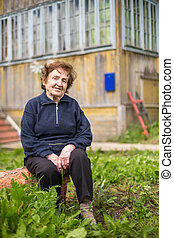Portrait elderly woman outdoors near her house.