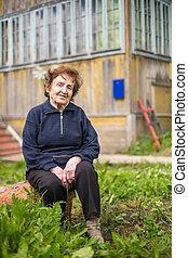 Portrait elderly woman outdoors near her house.