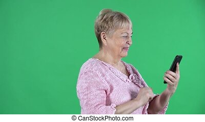 Portrait elderly woman talking on a video call using her smartphone. Gray haired grandmother with short hair in a pink sweater on green screen at studio. Side view. Close up.