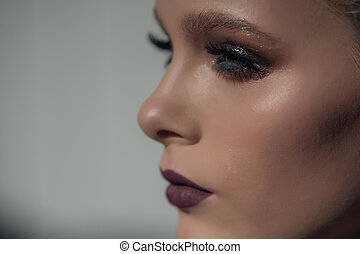 Portrait face in profile of a beautiful girl with professional makeup on white background