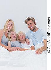 portrait, famille heureuse, lit